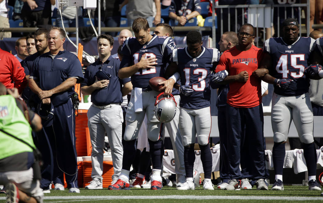 New England Patriots head coach Bill Belichick, left, and Tom Brady (12) Phillip Dorsett (13) Matthew Slater, second from right, and David Harris (45) stand during the national anthem before an NF ...