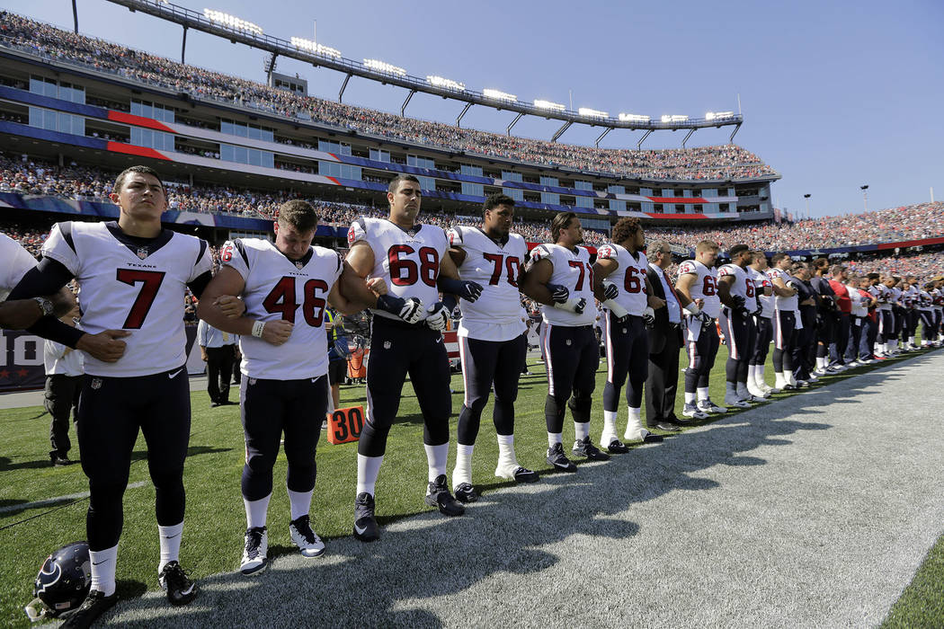 Members of the Houston Texans team stand with arms locked during the national anthem before an NFL football game against the New England Patriots, Sunday, Sept. 24, 2017, in Foxborough, Mass. (AP  ...