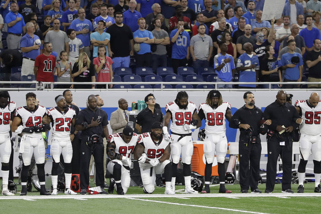 Atlanta Falcons defensive tackles Grady Jarrett (97) and Dontari Poe (92) take a knee during the national anthem before an NFL football game, Sunday, Sept. 24, 2017, in Detroit. (AP Photo/Carlos O ...
