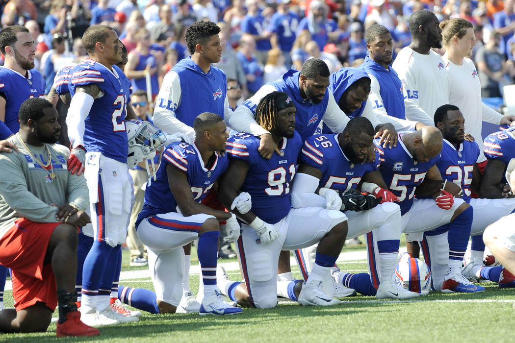 Buffalo Bills players take a knee during the national anthem prior to an NFL football game against the Denver Broncos, Sunday, Sept. 24, 2017, in Orchard Park, N.Y. (AP Photo/Adrian Kraus)