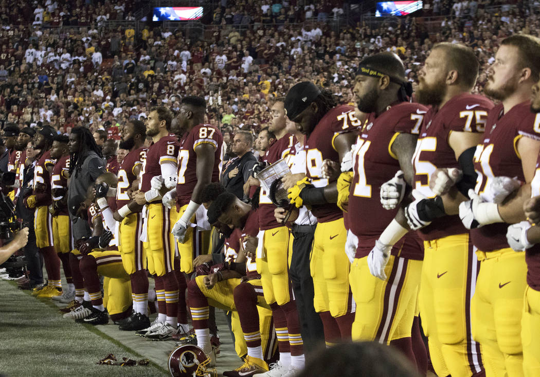 The Washington Redskins interlock arms during the national anthem before their game against the Oakland Raiders in Landover, Md., Sunday, Sept. 24, 2017. Heidi Fang Las Vegas Review-Journal @HeidiFang
