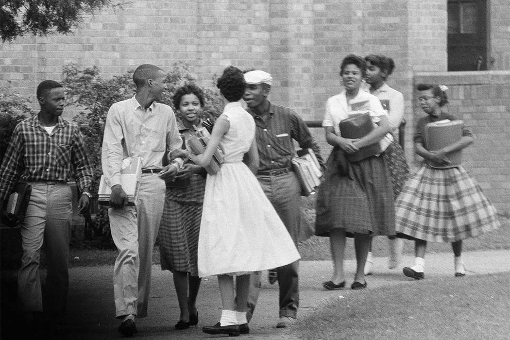 In this Oct. 2, 1957, file photo, the first black students to enroll at Central High School in Little Rock, Ark., leave the building and walk toward a waiting Army station wagon following their cl ...