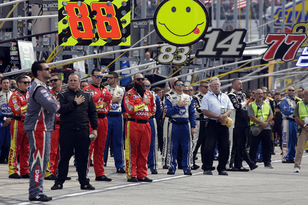 NASCAR teams crew members stand during the national anthem before a NASCAR Cup Monster Energy Series auto race at Chicagoland Speedway in Joliet, Ill., Sunday, Sept. 17, 2017. (AP Photo/Nam Y. Huh)