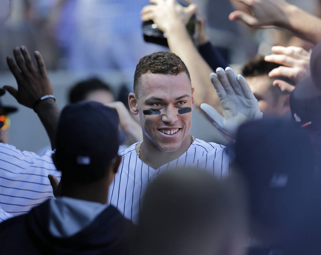 New York Yankees' Aaron Judge greets teammates in the dugout after hitting a two-run homer during the third inning of a baseball game against the Kansas City Royals at Yankee Stadium, Monday, Sept ...