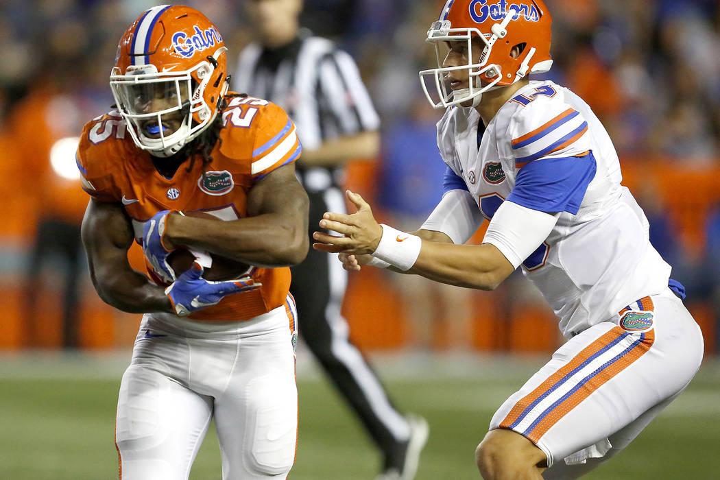This photo taken April 17, 2017, shows Florida running back Jordan Scarlett (25) takeing the handoff from quarterback Feleipe Franks (13) during the NCAA college football team's spring game in Gai ...