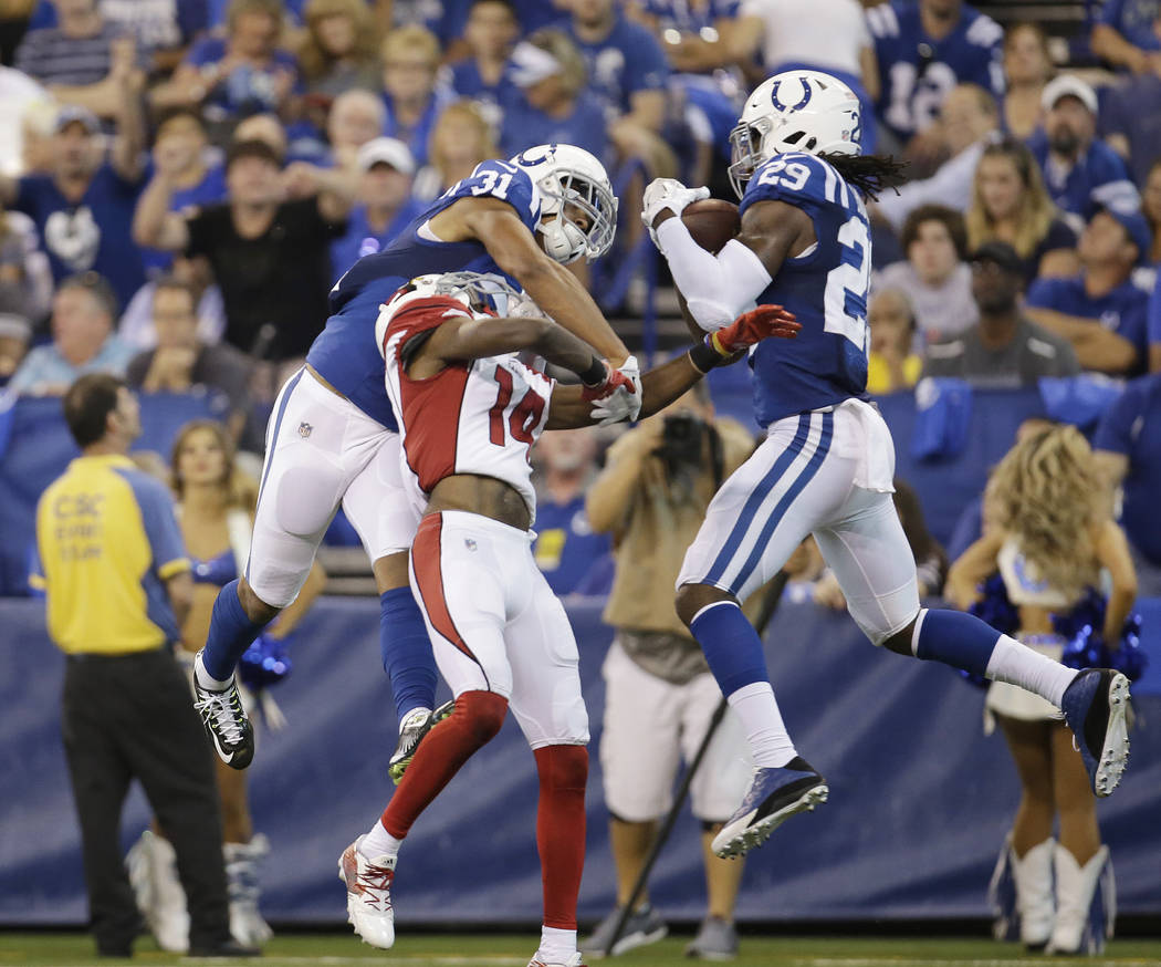 FILE - In this Sunday, Sept. 17, 2017, file photo, Indianapolis Colts' Malik Hooker (29) makes an interception on a pass intended for Arizona Cardinals' J.J. Nelson, center, during the first half  ...