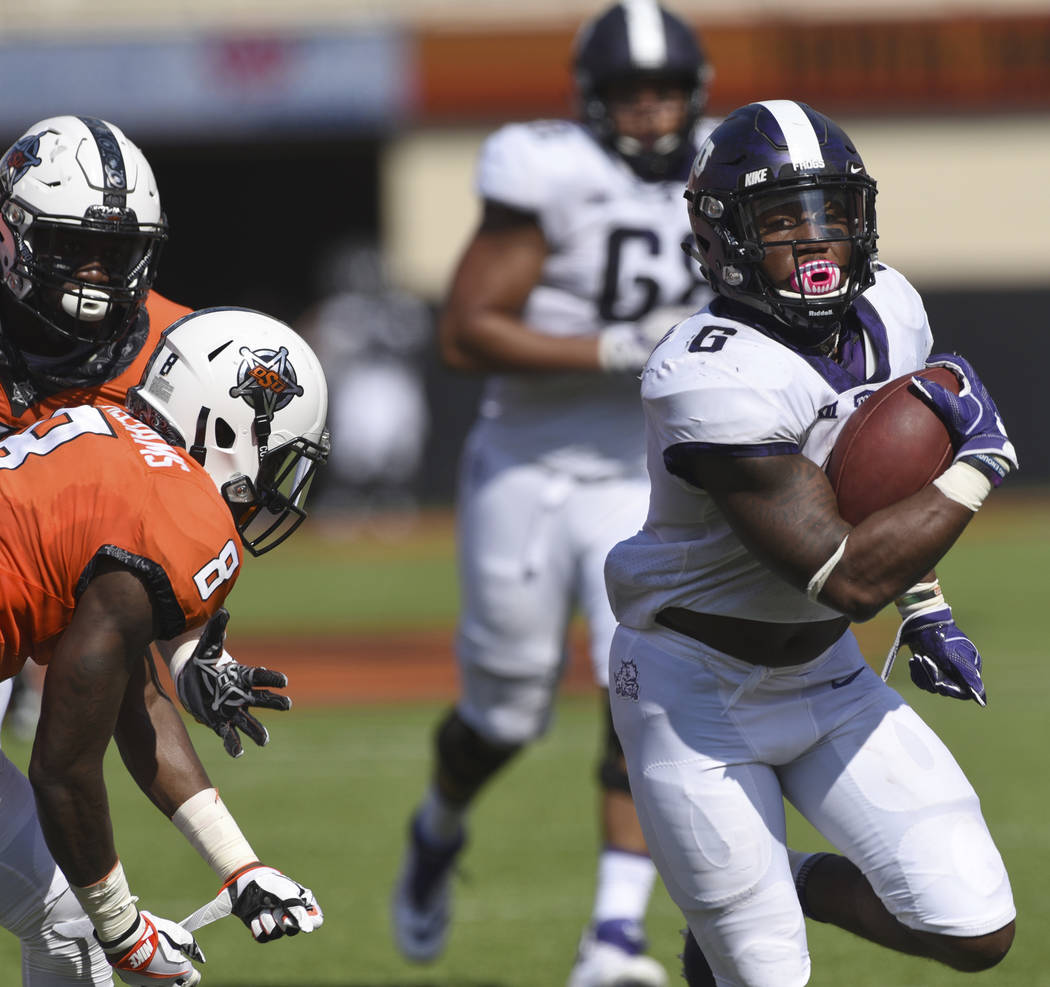 TCU running back Darius Anderson, right, break away from Oklahoma State defensive end Tralund Webber, left, and safety Za'Carrius Green to score a touchdown during the first half of an NCAA colleg ...