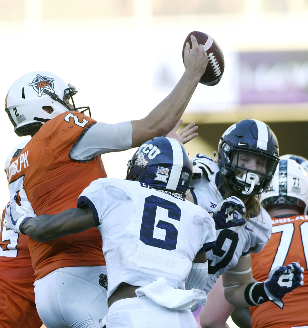 TCU safety Innis Gaines (6) pressures Oklahoma State quarterback Mason Rudolph (2) to throw a pass over TCU defensive end Mat Boesen (9) which was intercepted by TCU defensive end L.J. Collier, ha ...