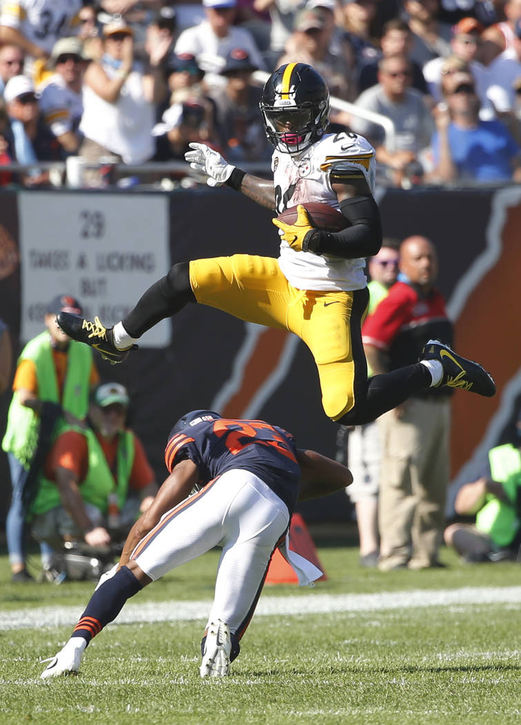 Pittsburgh Steelers running back Le'Veon Bell (26) leaps over Chicago Bears cornerback Kyle Fuller (23) during the second half of an NFL football game, Sunday, Sept. 24, 2017, in Chicago. (AP Phot ...