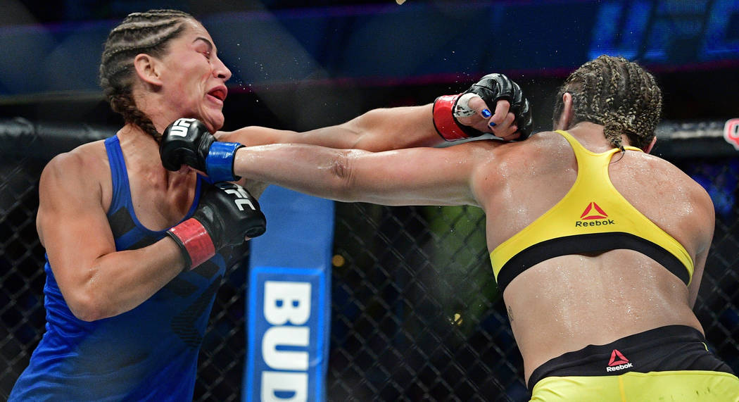 Bethe Correia, right, from Brazil, punches Jessica Eye during a women's bantamweight bout at UFC 203 on Saturday, Sept. 10, 2016, in Cleveland. (AP Photo/David Dermer)