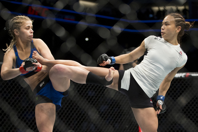 Paige VanZant, left, exchanges kicks against Michelle Waterson in the women's strawweight bout at the Golden 1 Center on Saturday, Dec. 17, 2016, in Sacramento, Calif. Waterson won by way o ...