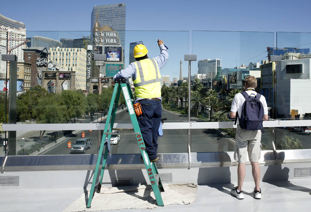 Elias Rios cleans glass panels on a pedestrian bridge linking the New York-New York and MGM Grand near Tropicana Avenue and Las Vegas Boulevard on Monday Sept. 25, 2017. The bridge had been closed ...