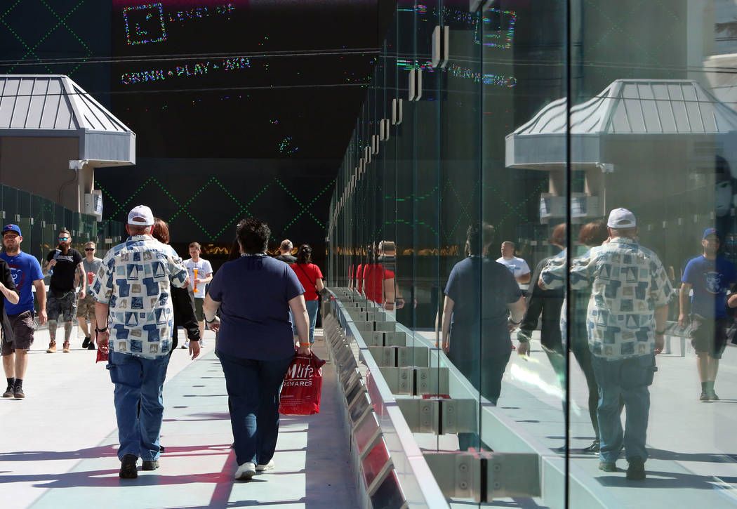 Tourists walk on a pedestrian bridge linking the New York-New York and MGM Grand near Tropicana Avenue and Las Vegas Boulevard on Monday Sept. 25, 2017. The bridge had been closed since July 5. Bi ...