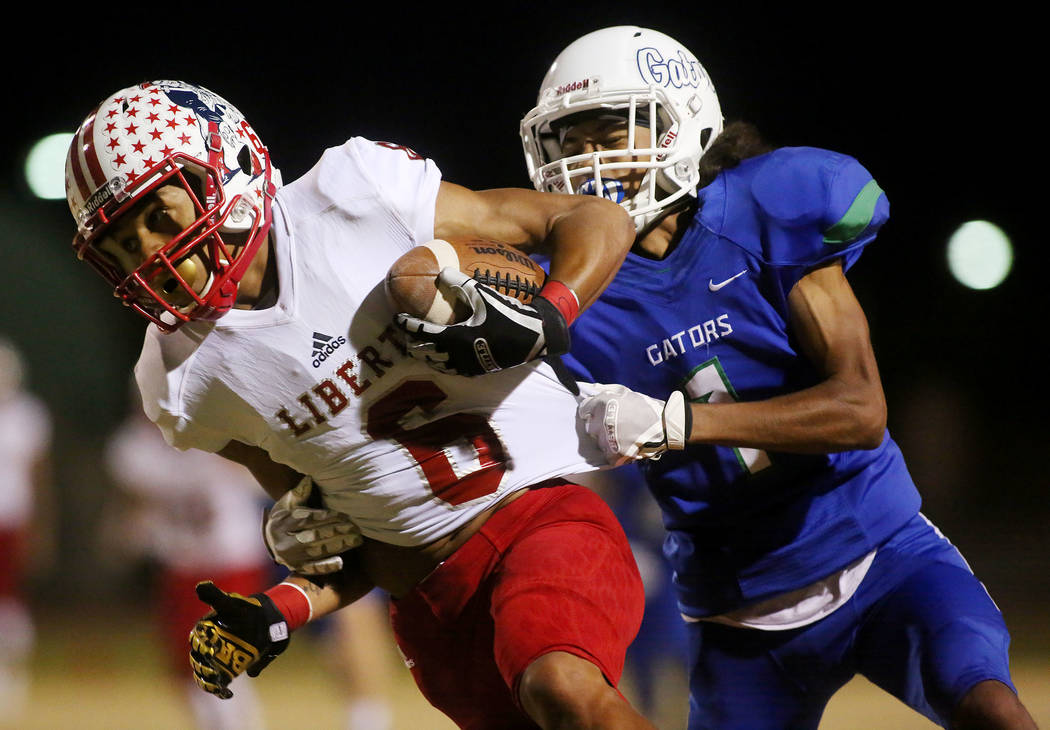 Green Valley player Daunte Watson (1) takes down Liberty player Cervontes White (6) during the first half of a game at Green Valley High School in Henderson, Thursday, Sept. 28, 2017. Bridget Benn ...