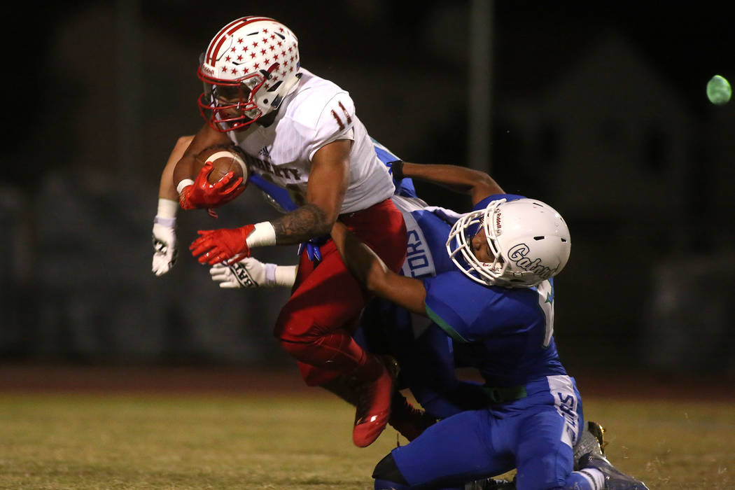 Green Valley player Antoin Kealoha (6) takes down Liberty player Jake Dedeaux (11) during the first half of a game at Green Valley High School in Henderson, Thursday, Sept. 28, 2017. Bridget Benne ...