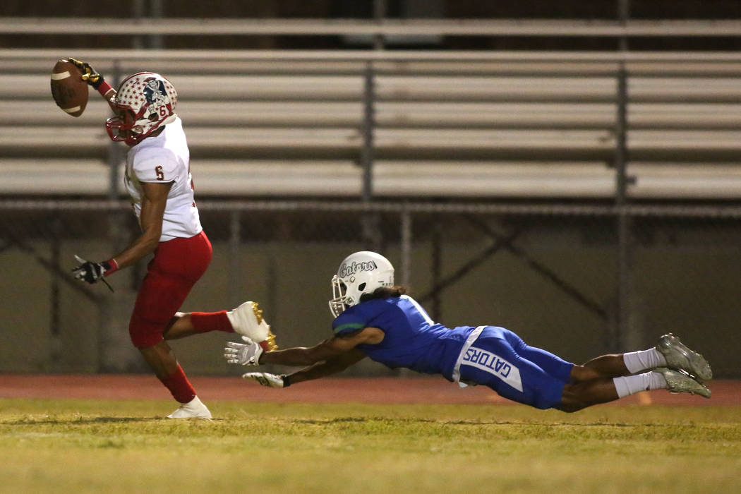 Green Valley player Daunte Watson (1) dives in attempts to tackle Liberty Cervontes White (6) during the first half of a game at Green Valley High School in Henderson, Thursday, Sept. 28, 2017. Br ...