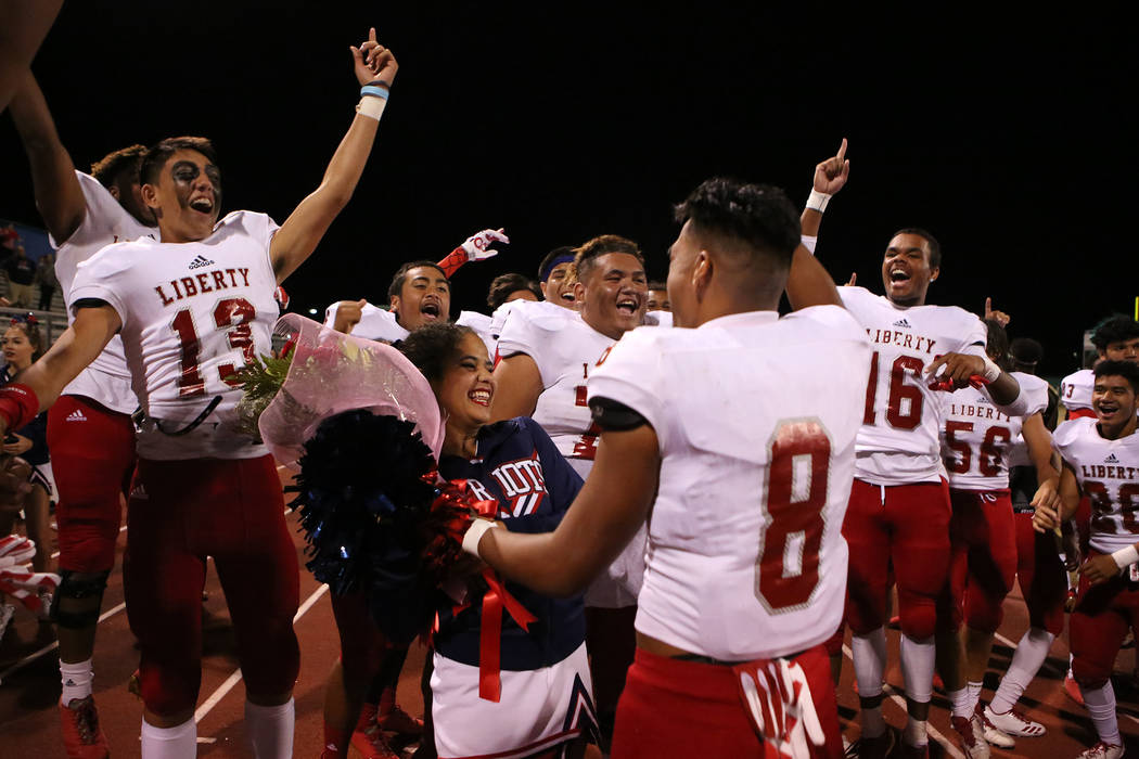 Liberty cheerleader Ciana Miller, left, smiles as she is asked to homecoming by Liberty football player Austin Fiaseu (8) after Liberty's 49-14 win over Green Valley at Green Valley High School in ...