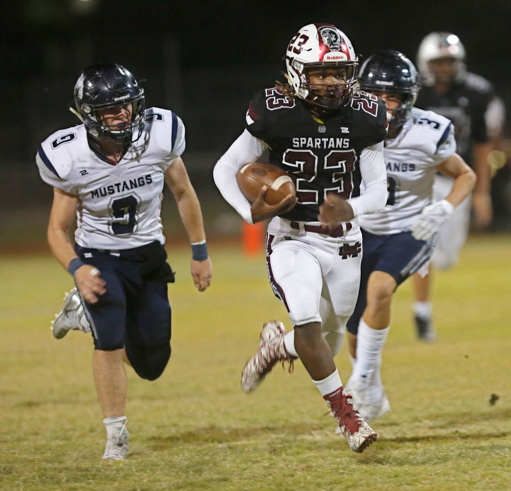 Cimarron-Memorial's Jordan Norwood  (23) carries a ball as Shadow Ridge's Chase Horlacher (9) and Travis Boston (3) go to stop him during the first half of a football game at Cimarron-Memorial Hig ...