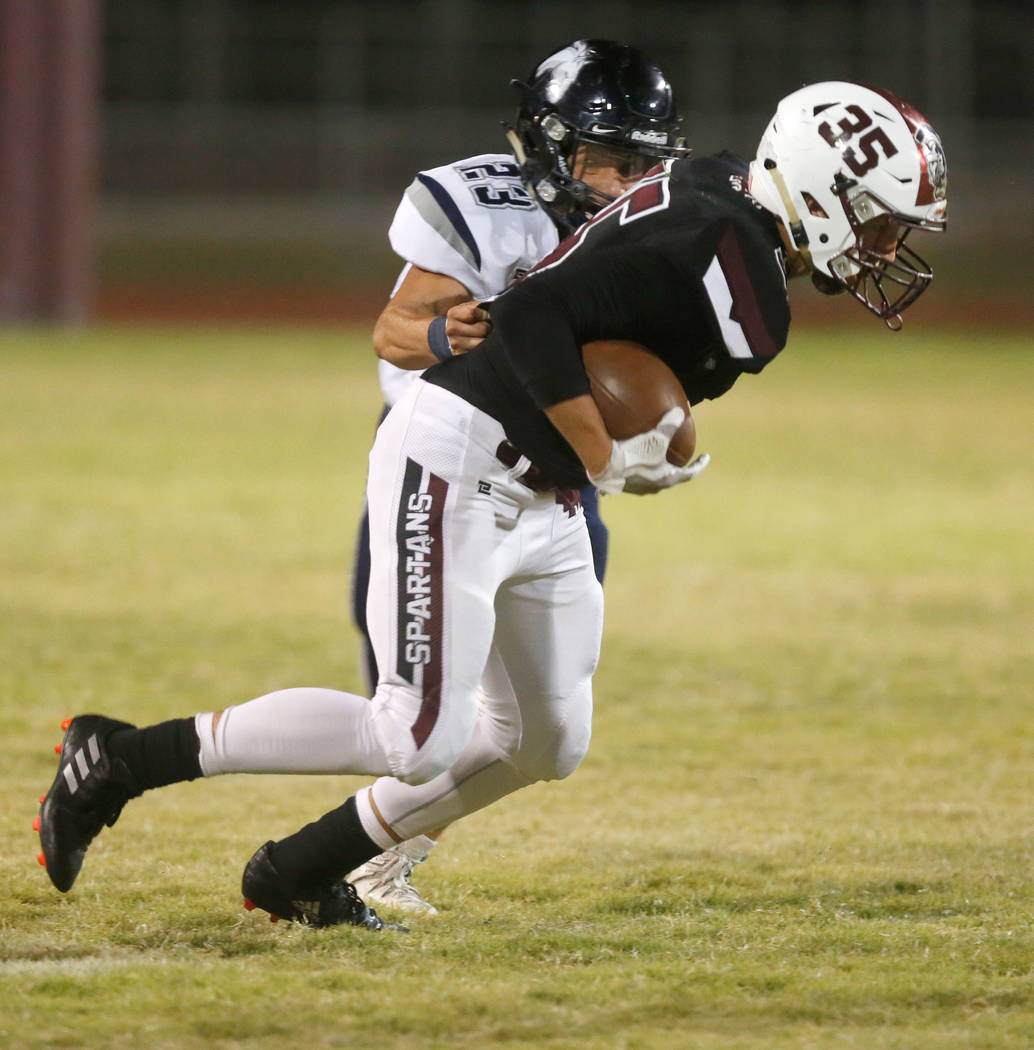 Cimarron-Memorial's Marcus Poole (35) keeps a ball away from Shadow Ridge's Sergio Martinez (23) during the first half of a football game at Cimarron-Memorial High School in Las Vegas, Thursday, S ...