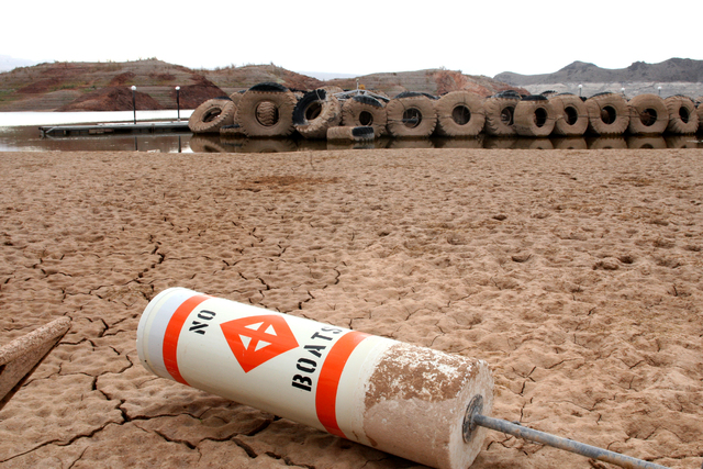 A buoy lies in the dried mud at Lake Mead's Echo Bay Marina in 2014. The U.S. and Mexico have reached a new treaty agreement that is expected to slow the decline of the lake and keep more water in ...