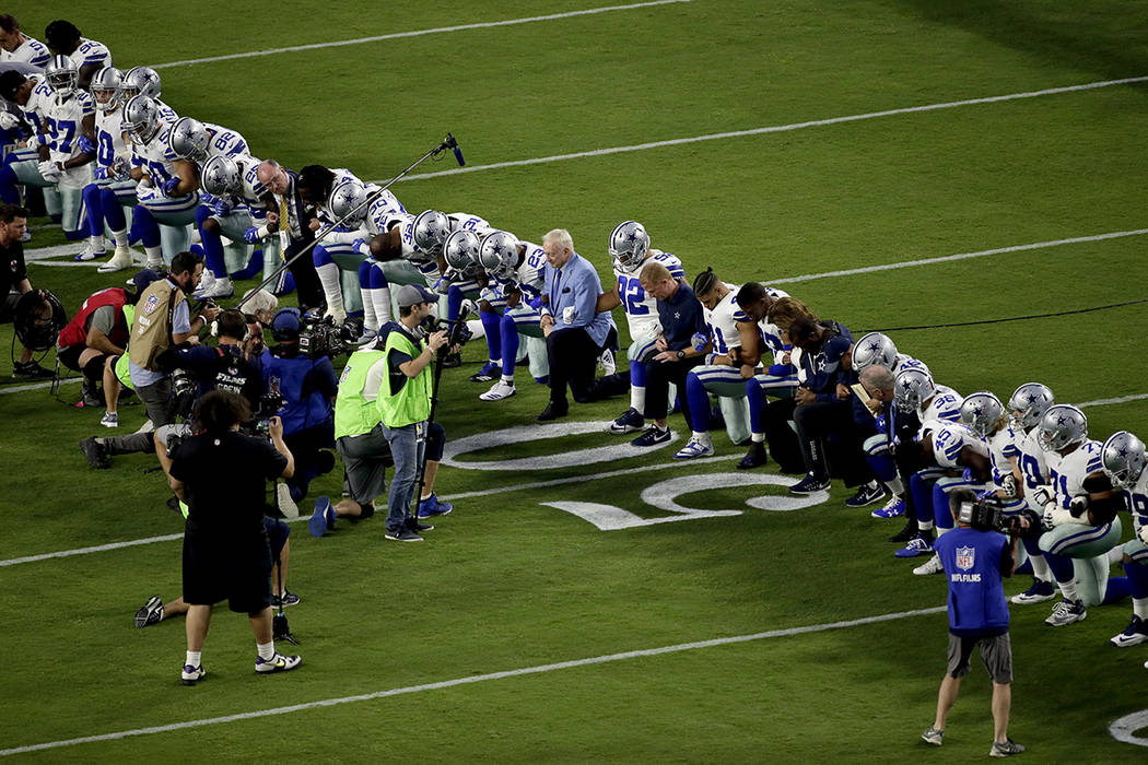 The Dallas Cowboys, led by owner Jerry Jones, center, take a knee prior to the national anthem prior to an NFL football game against the Arizona Cardinals, Monday, Sept. 25, 2017, in Glendale, Ari ...