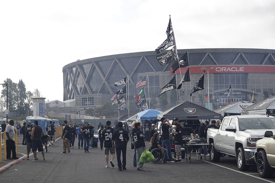 Fans tailgate at the Oakland Alameda County Coliseum parking lot before an NFL football game between the Oakland Raiders and the New York Jets in Oakland, Calif., Sunday, Sept. 17, 2017. (AP Photo ...