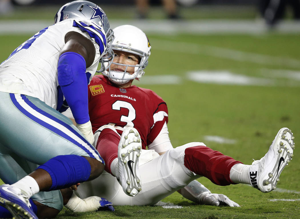 Arizona Cardinals quarterback Carson Palmer (3) looks at Dallas Cowboys defensive end Demarcus Lawrence after being sacked during the second half of an NFL football game, Monday, Sept. 25, 2017, i ...