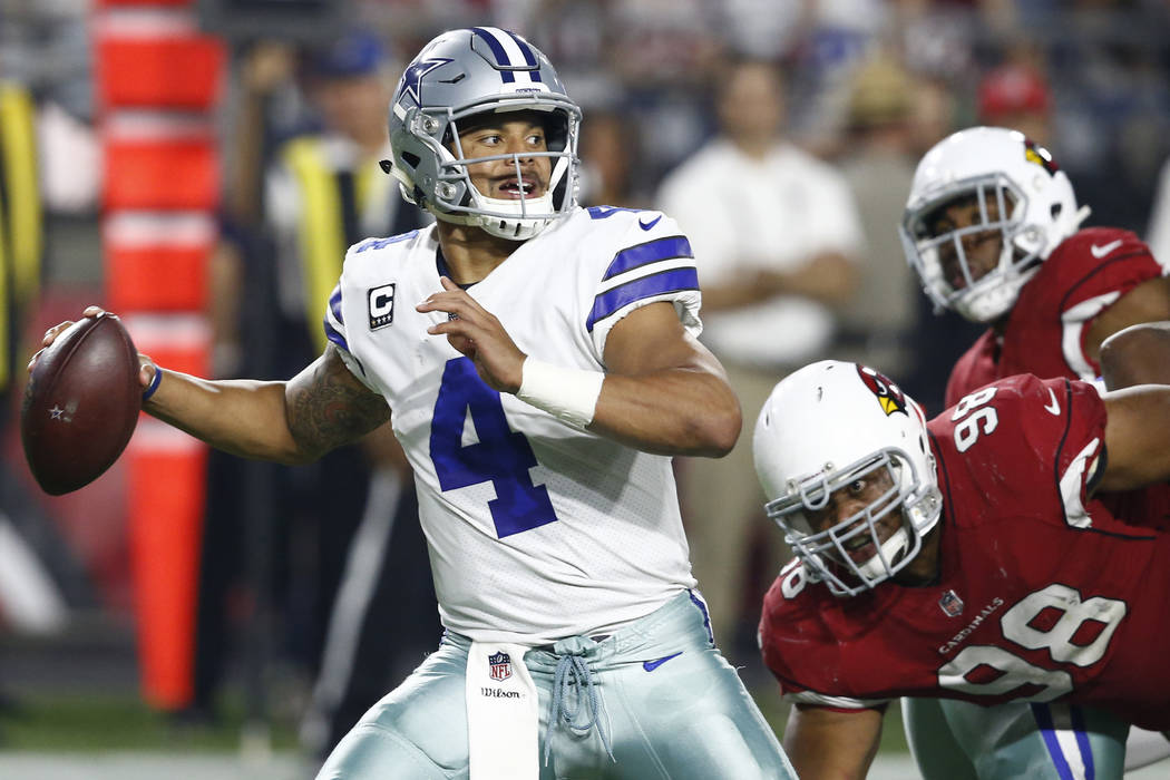 Dallas Cowboys quarterback Dak Prescott (4) throws as Arizona Cardinals nose tackle Corey Peters (98) pursues during the second half of an NFL football game, Monday, Sept. 25, 2017, in Glendale, A ...