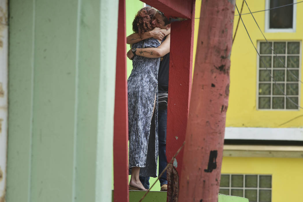 Residents at La Perla community in Old San Juan comfort one another as the community recovers from Hurricane Maria, in San Juan, Puerto Rico, Monday, Sept. 25, 2017. The island territory of more t ...