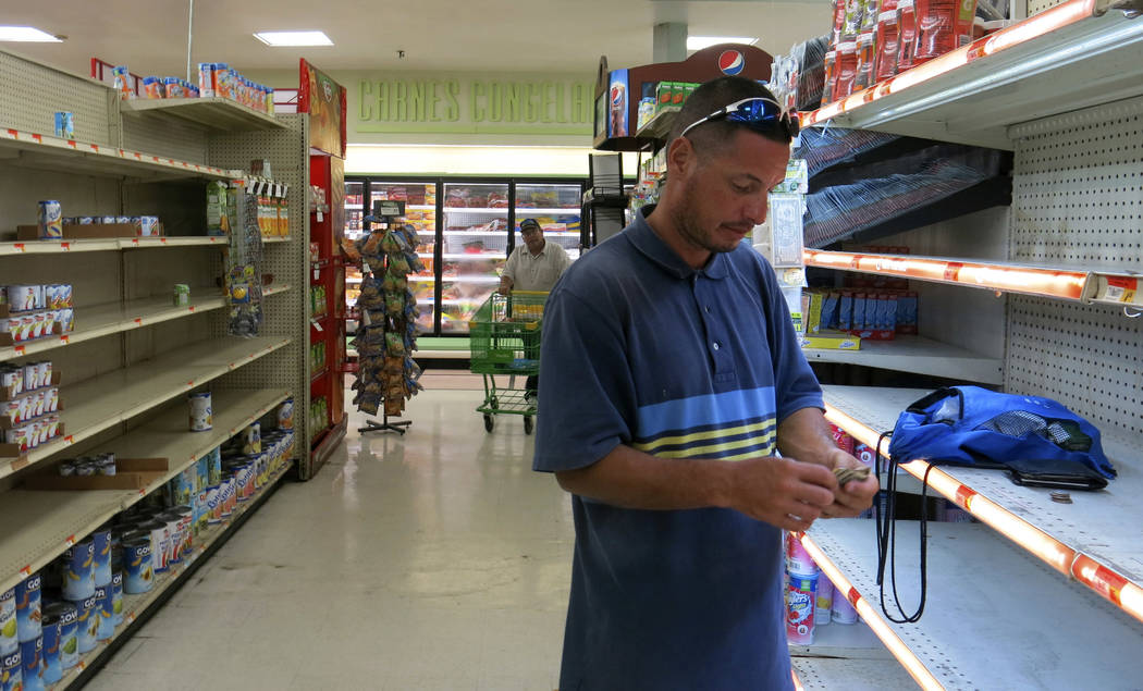 Christian Mendoza counts money in the aisle of a supermarket where he had hoped to buy water but only found cans of juice in San Juan, Puerto Rico, Monday Sept. 25, 2007. Bottled water was gone fr ...