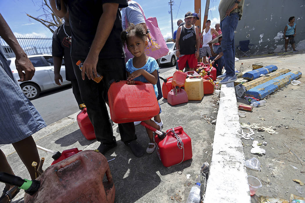 Abi de la Paz de la Cruz, 3, holds a gas can as she waits in line with her family, to get fuel from a gas station, in the aftermath of Hurricane Maria, in San Juan, Puerto Rico, Monday, Sept. 25,  ...