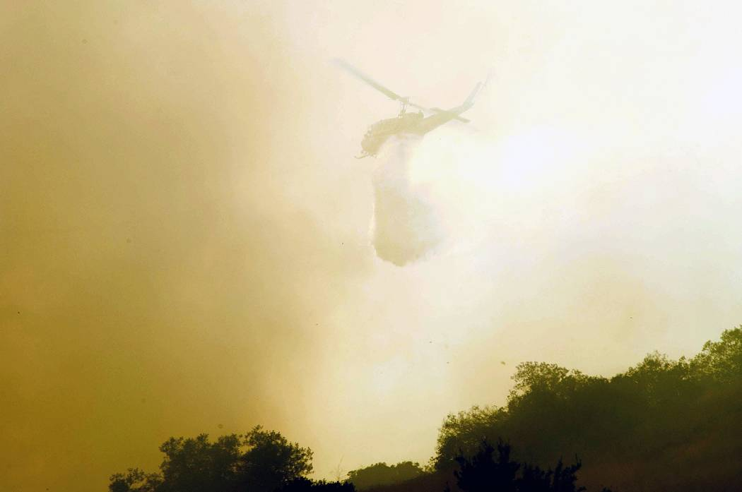 A helicopter makes a drop as a wildfire burns near State Route 91 near the Riverside County line in Anaheim Hills, Calif., Monday, Sept. 25, 2017. (Ken Steinhardt/The Orange County Register via AP)