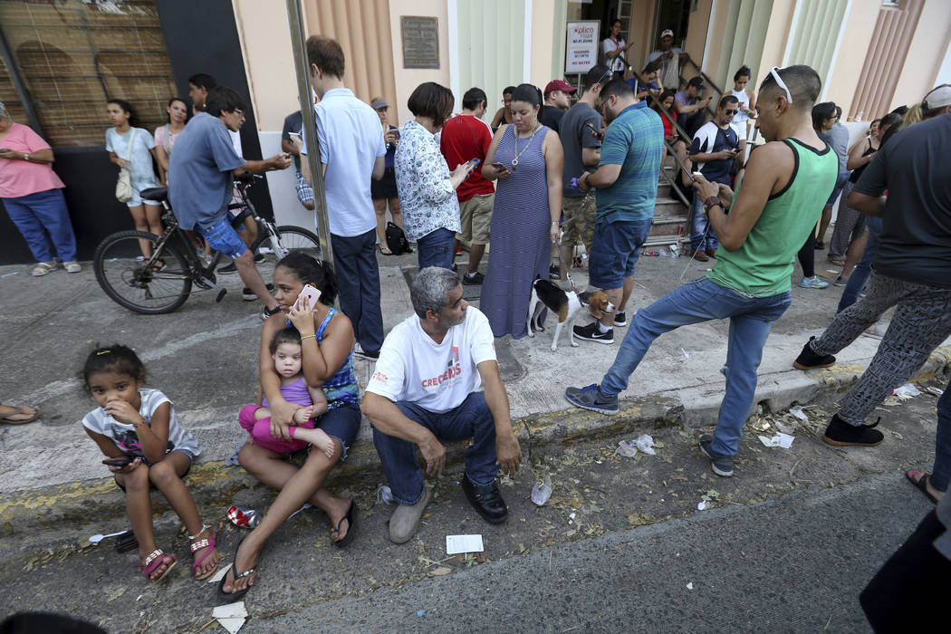 People use their devices to communicate as they congregate on the street at a wifi hotspot in San Juan, Puerto Rico, in the aftermath of Hurricane Maria, Sunday, Sept. 24, 2017. Federal aid is rac ...