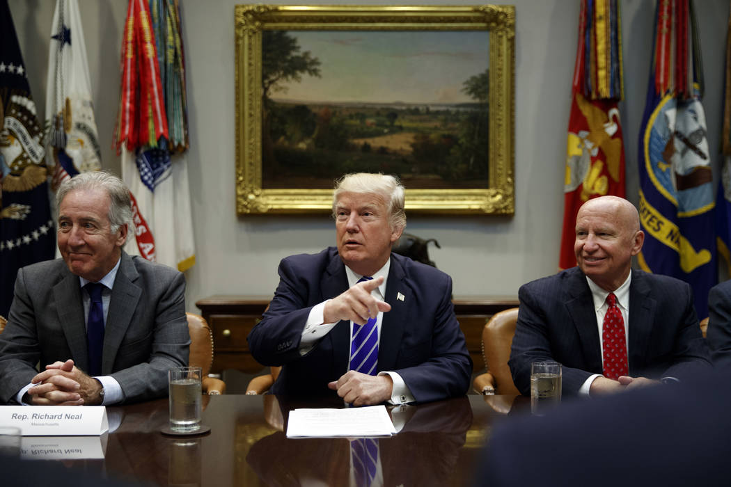 Rep. Richard Neal, D-Mass., left, and Rep. Kevin Brady, R-Texas, right, listen as President Donald Trump speaks during a meeting with members of the House Ways and Means committee in the Roosevelt ...