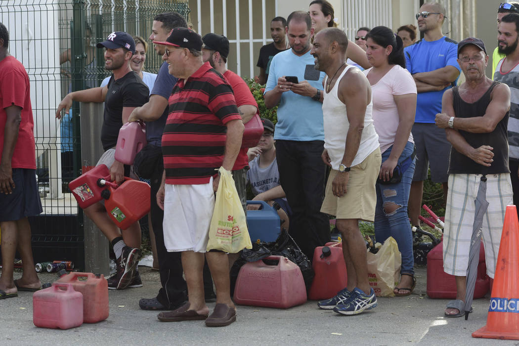 Hundreds of people wait in line since the early morning hours to buy gasoline on the third day after the impact of Hurricane Maria, in San Juan, Puerto Rico, Saturday, Sept. 23, 2017. Many were un ...