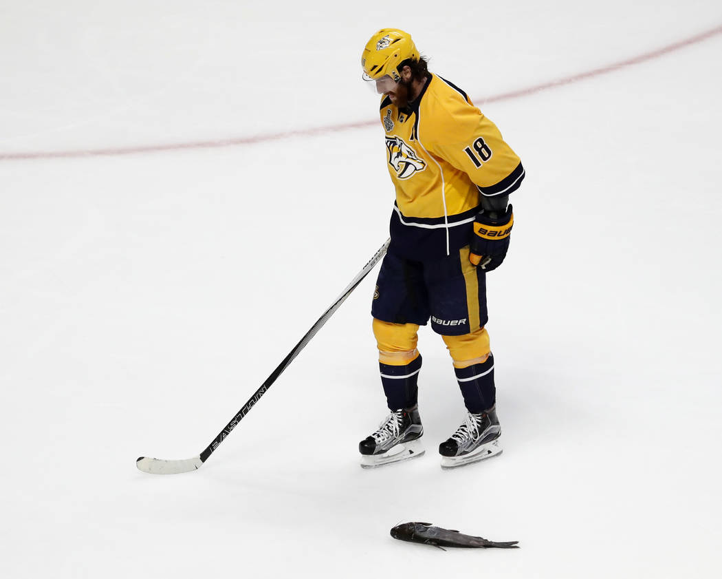Nashville Predators' James Neal (18) skates by a catfish thrown onto the ice during the third period of Game 6 of the NHL hockey Stanley Cup Final against the Pittsburgh Penguins, Sunday, June 11, ...