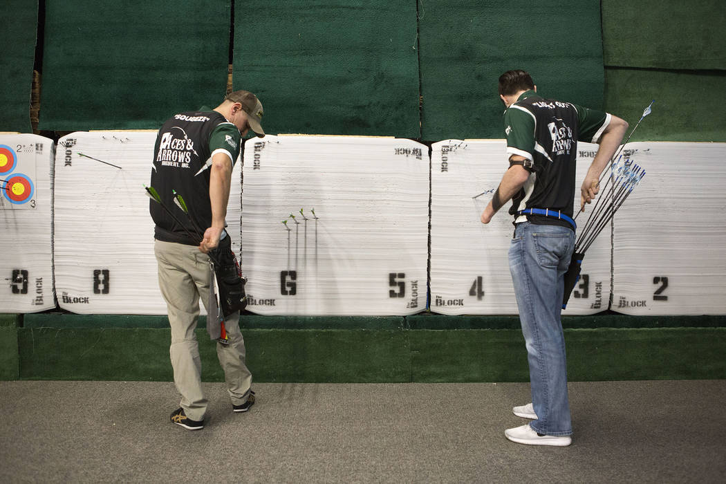AJ Hanagata, left, and Ryan Sidor pull their arrows after shooting at Aces and Arrows in Henderson, Thursday, Sept. 28, 2017. The two opened Aces and Arrows, a store and 22-lane range, in August.  ...