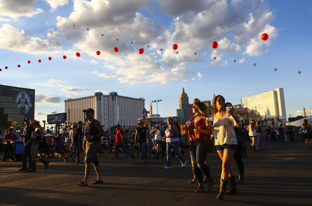 Attendees walk the festival grounds during the Route 91 Harvest country music festival at the MGM Resorts Village festival site in Las Vegas on Friday, Sept. 30, 2016. (Chase Stevens/Las Vegas Rev ...