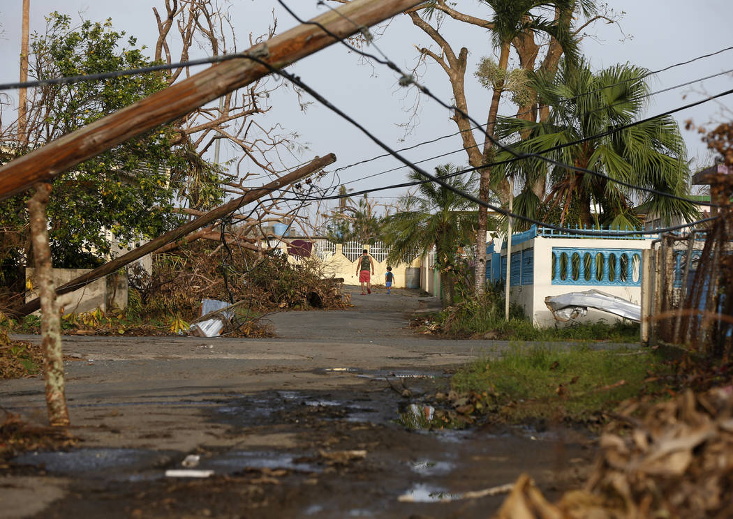 A man and child walk down street strewn with debris and downed power lines in the aftermath of Hurricane Maria, in Yabucoa, Puerto Rico, Tuesday, Sept. 26, 2017. (Gerald Herbert/AP)