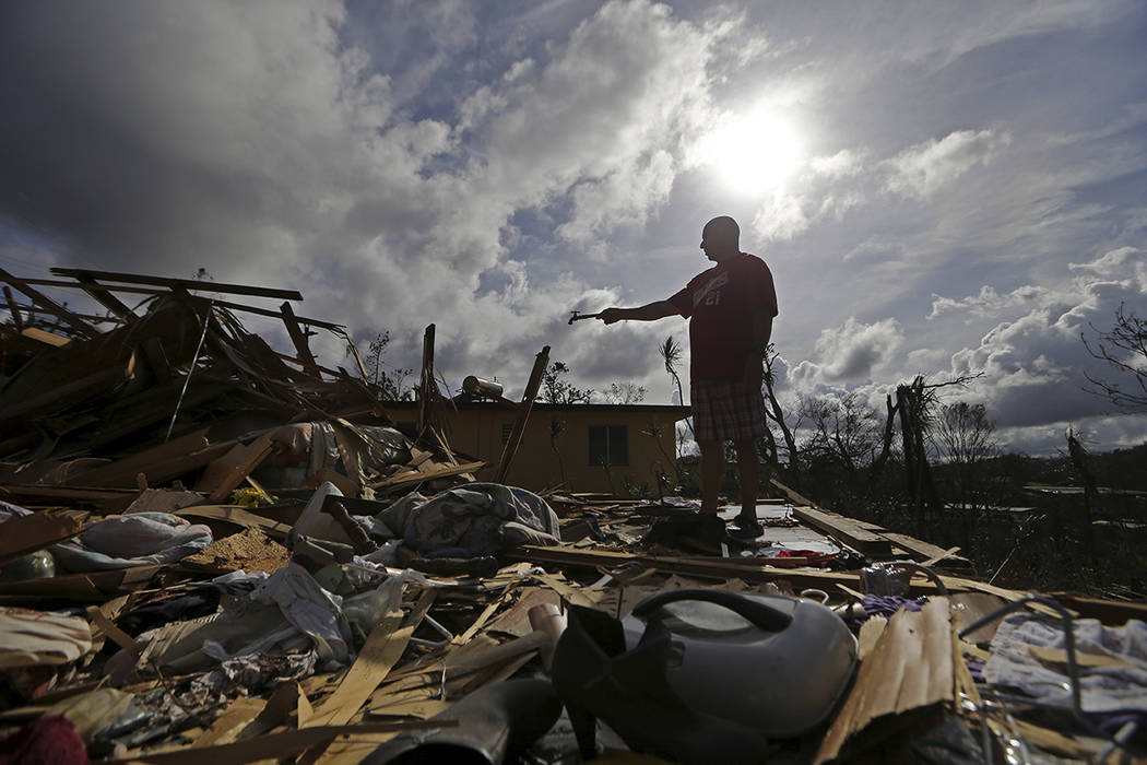 Jose Garcia Vicente holds a piece of plumbing he picked up, as he shows his destroyed home, in the aftermath of Hurricane Maria, in Aibonito, Puerto Rico, Monday, Sept. 25, 2017. The U.S. ramped u ...