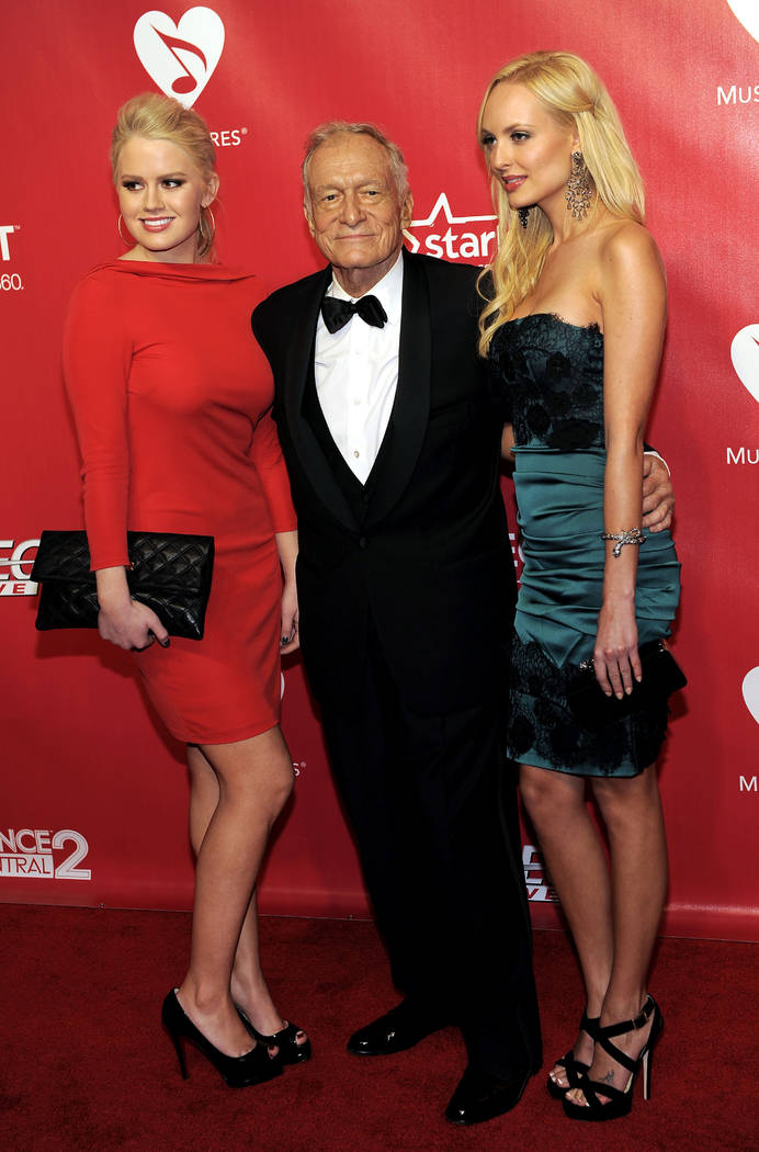 Hugh Hefner, center, Anna Sophia Berglund, left, and Shera Bechard arrive at the MusiCares Person of the Year gala honoring Paul McCartney on Friday, Feb. 10, 2012 in Los Angeles. (AP Photo/Chris  ...