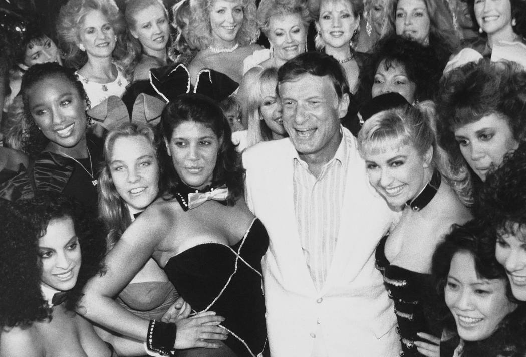 FILE - In this June 25, 1986 file photo, Playboy founder Hugh Hefner, center, poses with a group of current and former Playboy bunnies at the Playboy Club in Los Angeles, days before the club clos ...