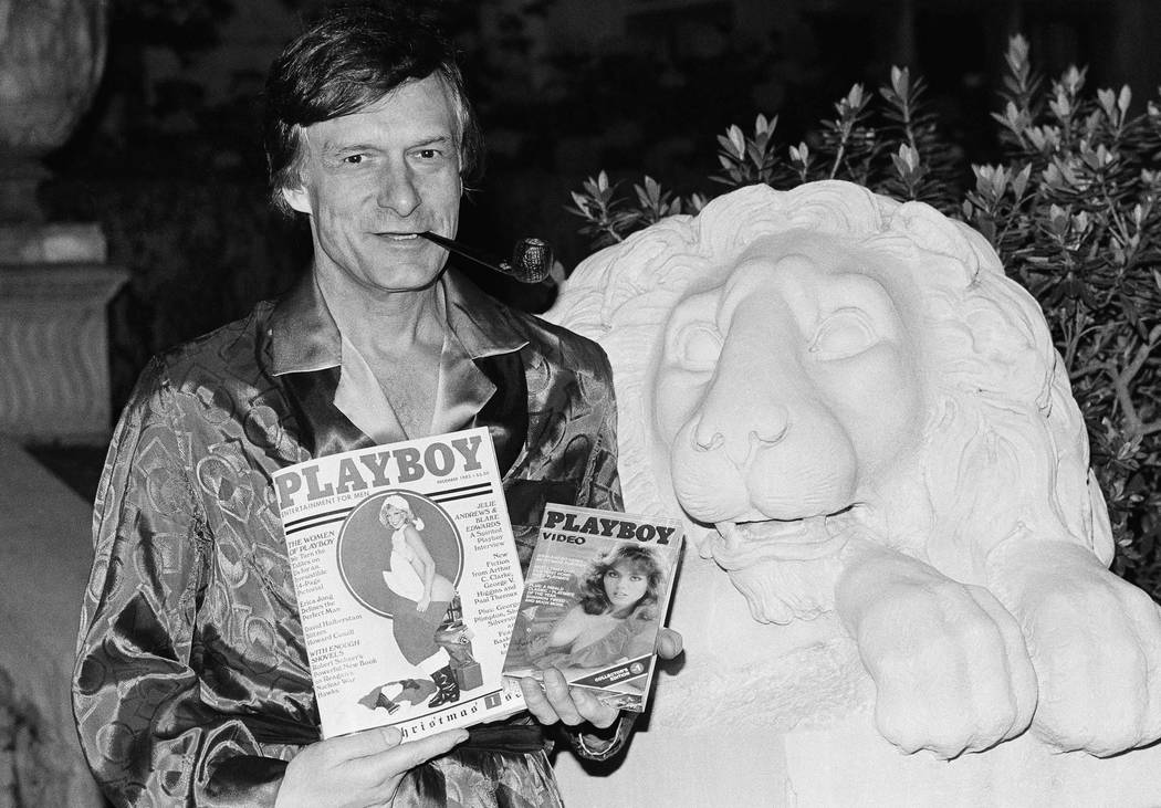 Playboy magazine publisher Hugh Hefner holds a copy of the magazine and a video cassette from the Playboy Channel, an all-night cable television venture Playboy Enterprises has undertaken, during  ...