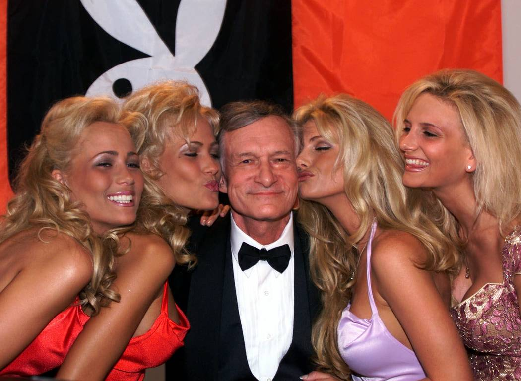 Playboy founder and editor in chief Hugh Hefner receives kisses from Playboy playmates in Cannes, France, Friday, May 14, 1999 during the 52nd Cannes Film Festival. (AP Photo/Laurent Rebours)