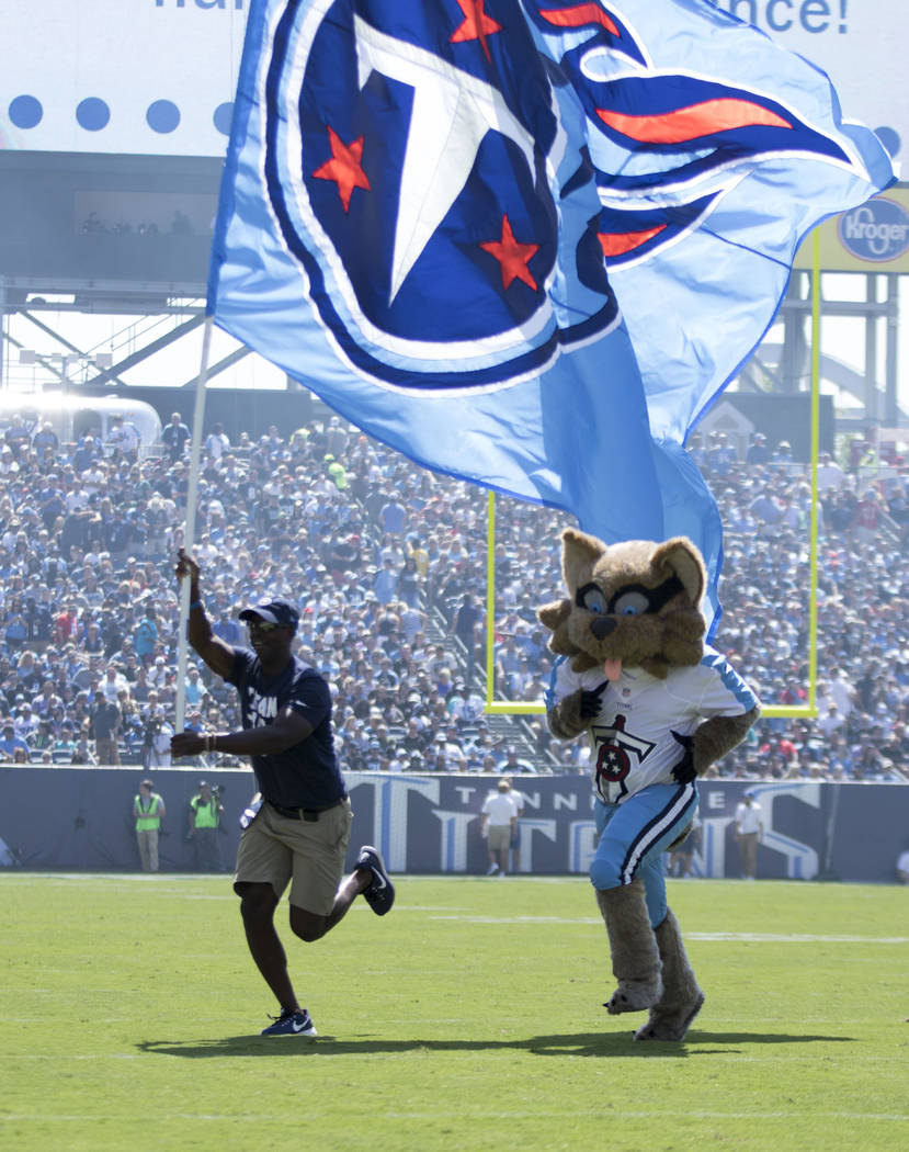 A flag runner with the Tennessee Titans mascot after the team scored against the Oakland Raiders in the first half of their game at the Nissan Stadium in Nashville, Tenn., Sunday, Sept. 10, 2017.  ...