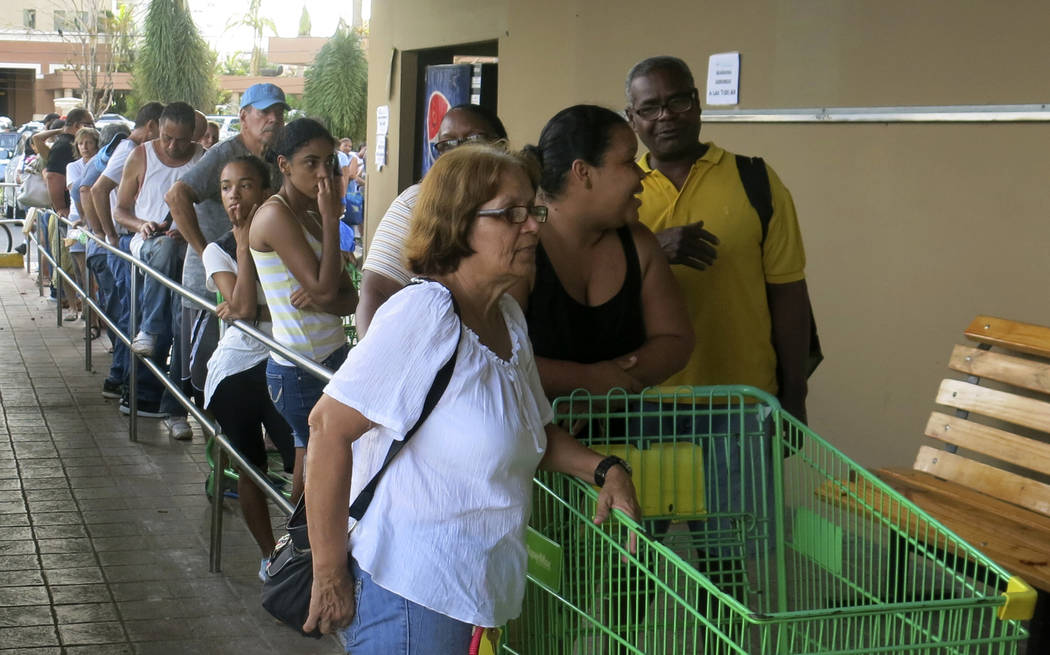 People wait in line outside a grocery store to buy food that wouldn't spoil and that they could prepare without electricity, in San Juan, Monday, Sept. 25, 2017. Most stores and restaurants remain ...