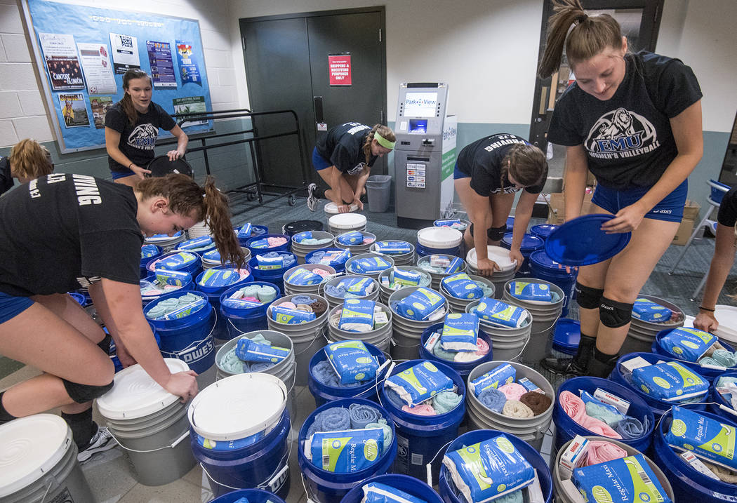 In this Sept. 25, 2017, photo, members of the community join the Eastern Mennonite University volleyball team as they pack buckets with relief kits bound for hurricane-ravaged Puerto Rico in Harri ...