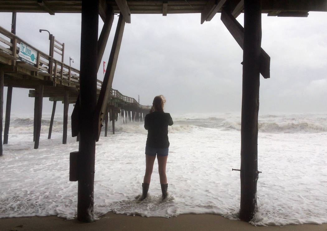 A woman stands in the water as Hurricane Maria moves closer to North Carolina's Outer Banks on Tuesday, Sept. 26, 2017. Thousands of visitors abandoned their vacation plans and left the area as th ...
