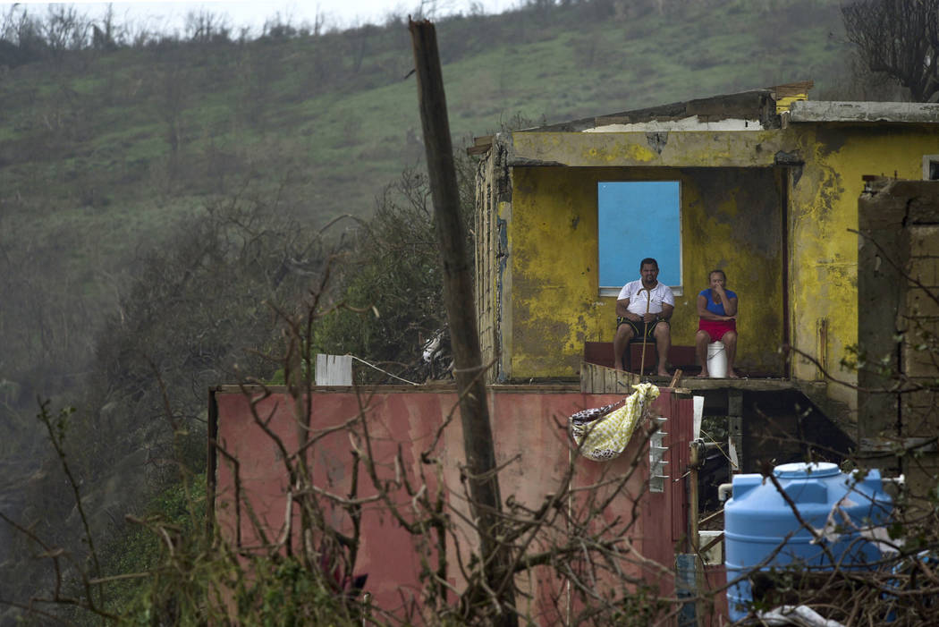 FILE - In this Thursday, Sept. 21, 2017, file photo, a couple sits in their home in El Negro, Puerto Rico, a day after the impact of Hurricane Maria. Maria has devastated Puerto Rico, destroying b ...