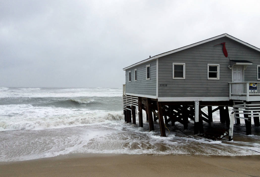 Waves wash ashore hitting a house as winds and storm surge from Tropical Storm Maria lash North Carolinas Outer Banks as the storm moves by well off-shore on Wednesday, Sept. 27, 2017. Dare County ...
